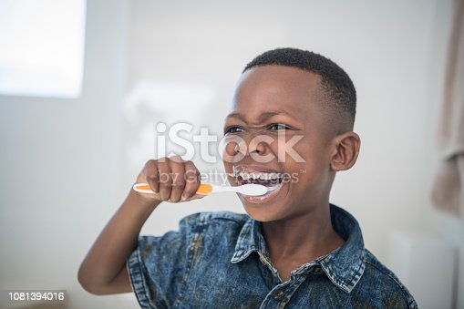 Head and shoulders of young boy wearing denim shirt, using toothbrush with toothpaste on hi lips, mouth open, getting ready in the morning, dental hygiene, oral care
