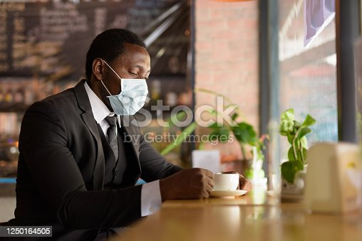 Portrait of African businessman with mask for protection from corona virus outbreak relaxing at the coffee shop indoors