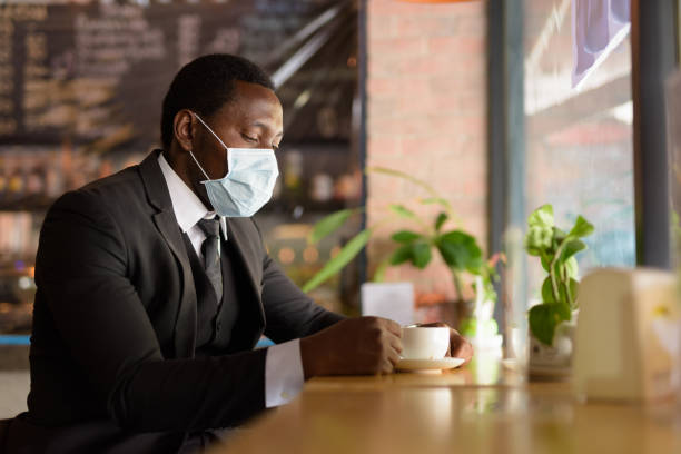 Portrait of African businessman wearing mask while drinking coffee inside the coffee shop as the new normal stock photo