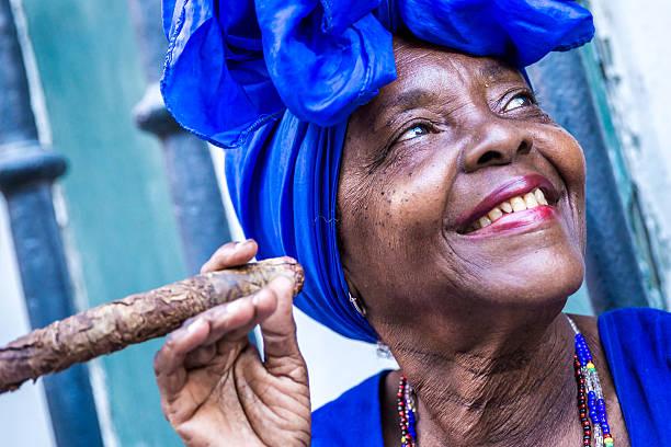 portrait of african cuban woman smoking cigar in havana, cuba - cuba stock photos and pictures