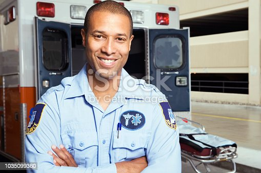 Portrait of African male paramedic in front of ambulance