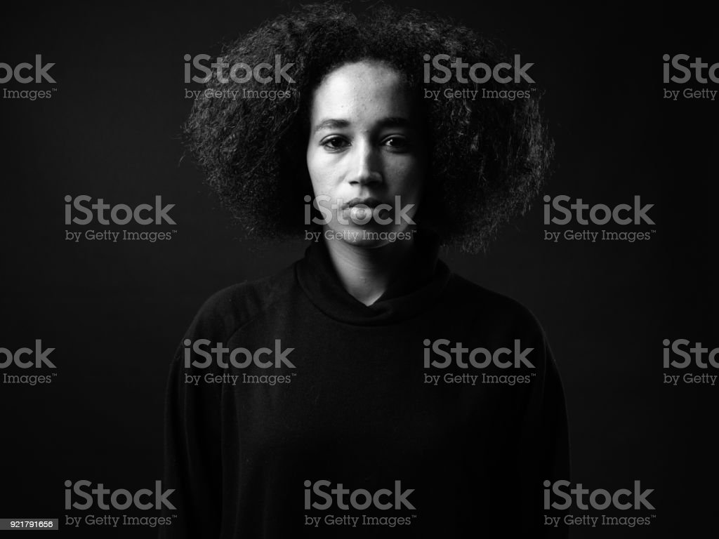Portrait Of African Woman Against Black Background stock photo