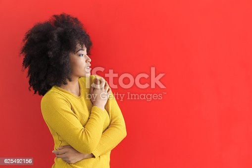 istock Portrait of african woman on red background 625492156