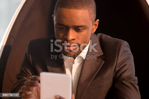 istock Portrait of african-american businessman sitting in chair holding mobile tablet 695760102