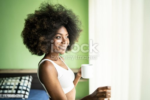 Young woman with afro hair drinking coffee in the morning