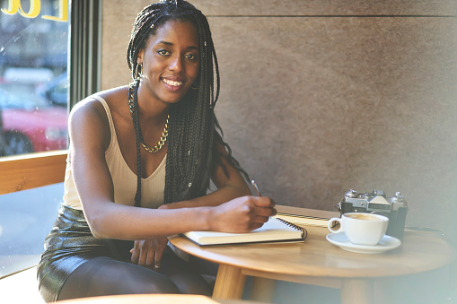 istock Portrait of afro american correspondent working on research cool cafe places for media sitting indoors and looking at camera.Smiling creative photographer writing ideas for photo session in notebook 908018174