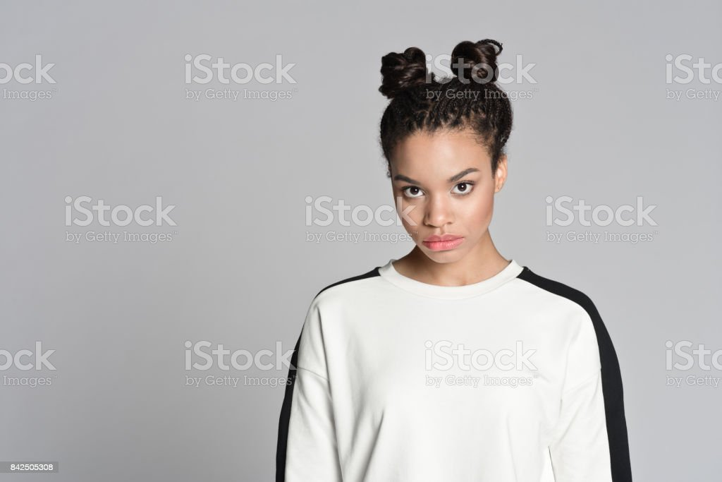 Portrait of afro american cute teenager girl Studio portrait of afro american cute teenage woman. Studio shot, grey background. 16-17 Years Stock Photo