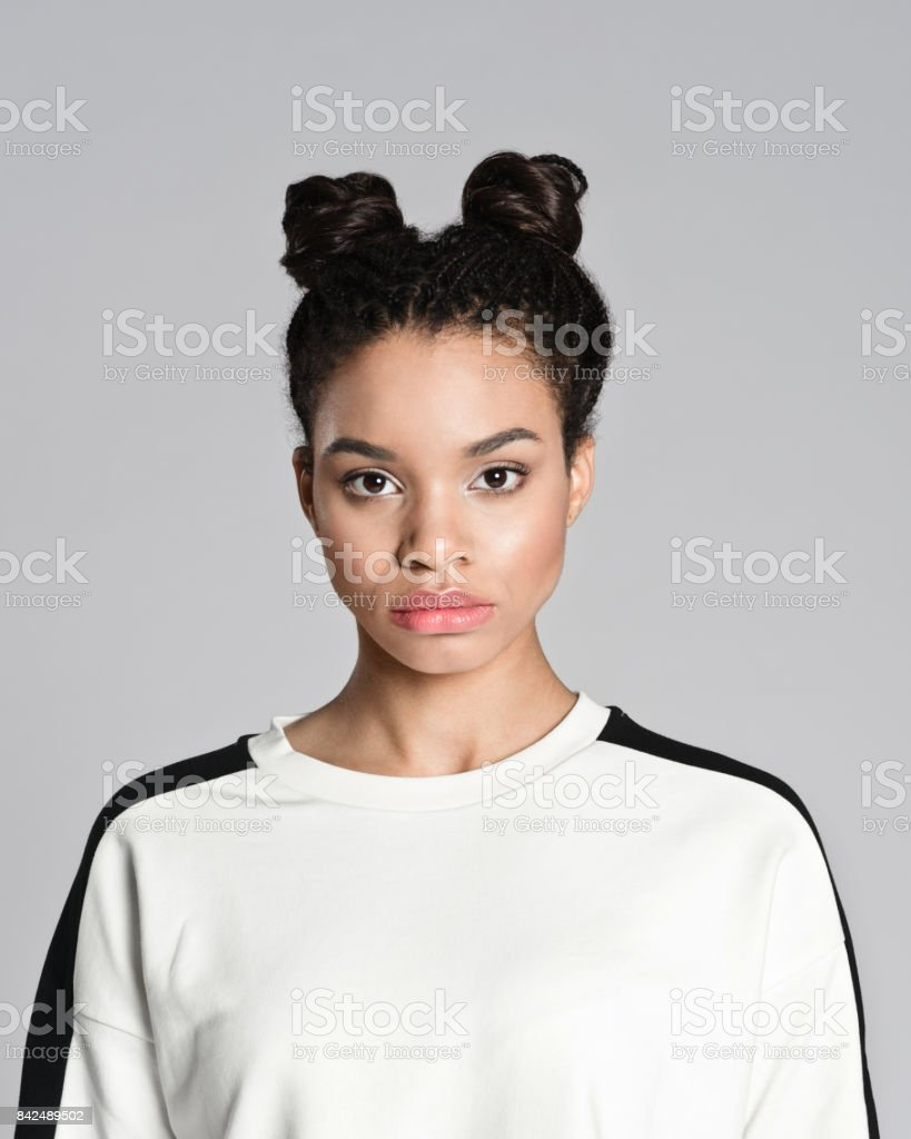 Portrait of afro american teenager woman Studio portrait of afro american teenage woman looking at camera. Studio shot, grey background. 16-17 Years Stock Photo