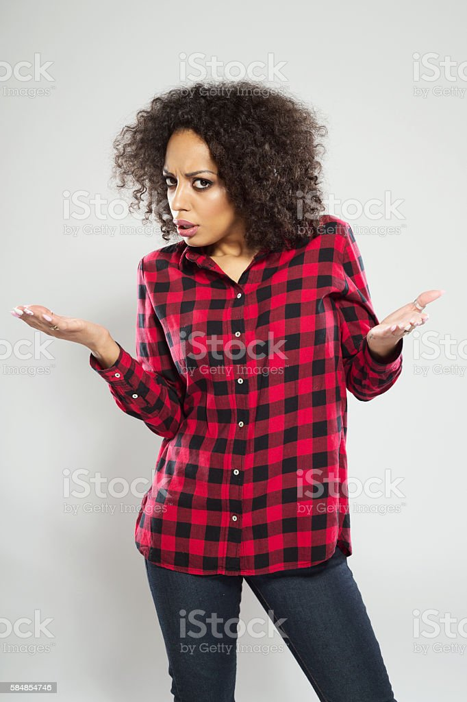 Portrait of afro american young woman Portrait of displeased afro american young woman wearing casual red checkered shirt, standing against grey background with raised hands. Adult Stock Photo