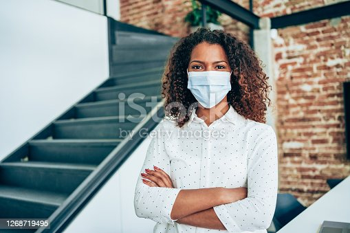 Portrait of afro-american businesswoman wearing face protective mask at the office.