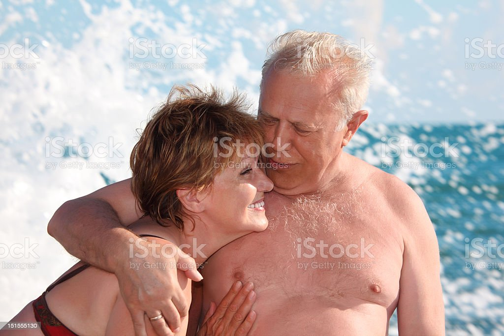 Portrait of aged pair in sea surf stock photo