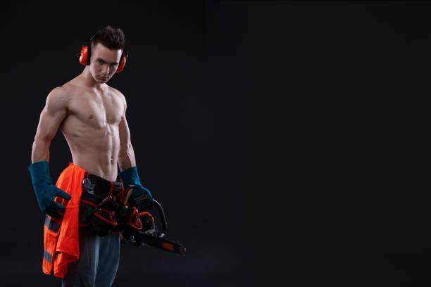 porträt von aggressiven muskulöser mann mit kettensäge in der hand, posiert auf schwarzem hintergrund. baumeister - killer workouts stock-fotos und bilder