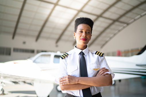 Portrait of airplane pilot in a hangar and looking at camera