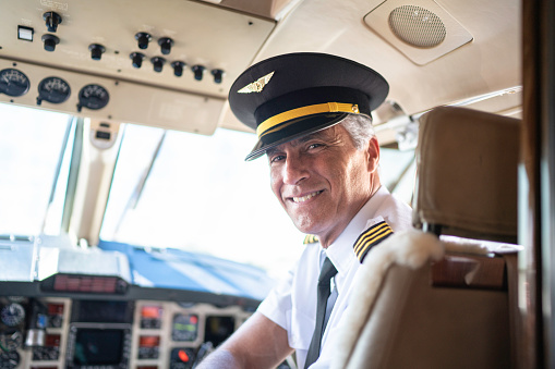 Portrait of airplane pilot looking over shoulder in a private jet