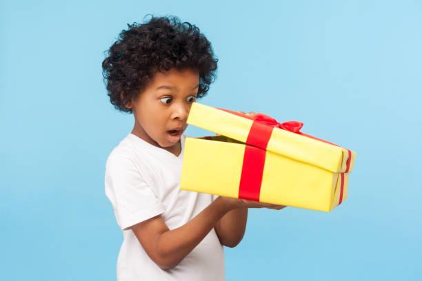 ギフトボックスの中を覗く驚いた好奇心旺盛な愛らしい小さな男の子の肖像画、面白い驚きの表情でプレゼントを開梱 - 誕生日の贈り物 ストックフォトと画像