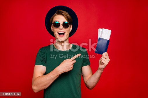 Portrait of amazed excited brunette hair tourism lover guy travel on weekends, hold tickets point index finger scream wow omg wear blue headwear green t-shirt isolated over red color background
