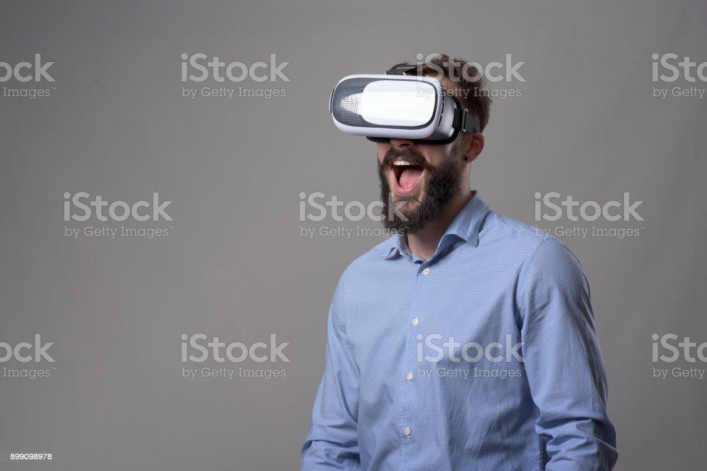 Portrait d'étonné homme barbu de jeune excité, je regarde les lunettes de réalité virtuelle avec l'expression de la bouche ouverte - Photo