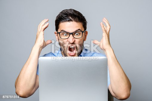 istock Portrait of amazed man with laptop computer over gray background 879751314