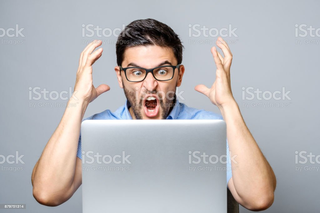 Portrait of amazed man with laptop computer over gray background stock photo