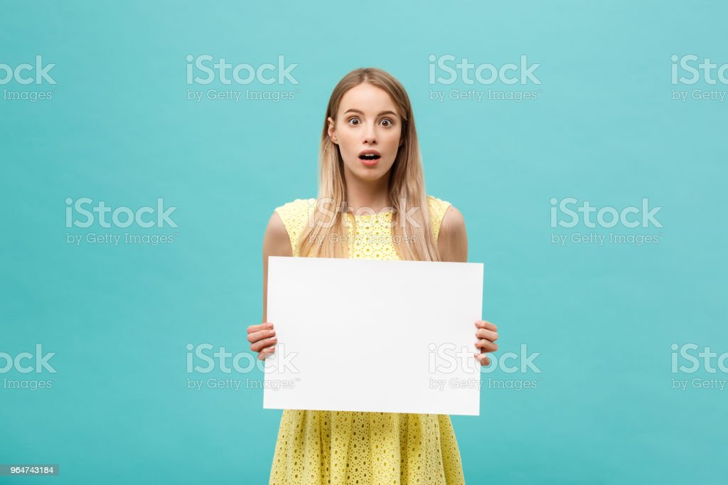 Portrait of amazed young blond woman holding blank sign with copy space on blue studio background. Showing shocked surprise face. royalty-free stock photo
