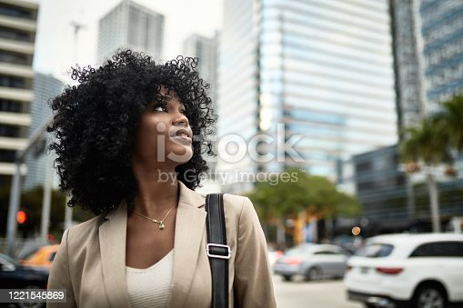 Front view of 21 year old African-American female corporate professional looking up and away from camera with optimistic expression in downtown Miami.