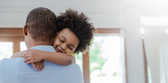 Portrait of american african father and son hugging laughing in living room. Happy daddy and his little boy spending leisure time at home. Single dad, family lifestyle father's day concept banner