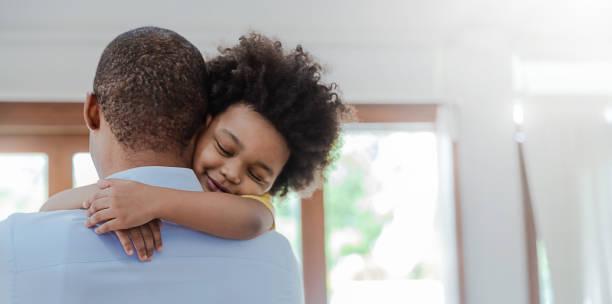 porträt des amerikanischen afrikanischen vaters und sohnes, der lachend im wohnzimmer umarmt. glücklicher papa und sein kleiner junge verbringen freizeit zu hause. alleinerziehender vater, familie lifestyle vater tag konzept banner - genderblend stock-fotos und bilder