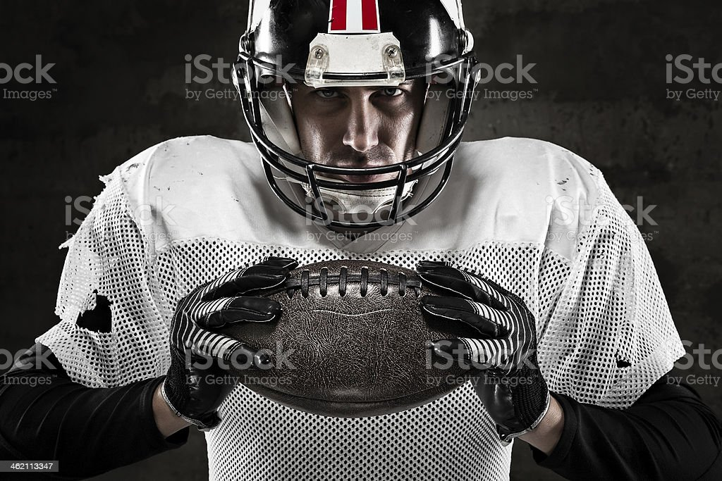 Portrait of american football player holding a ball and looking stock photo