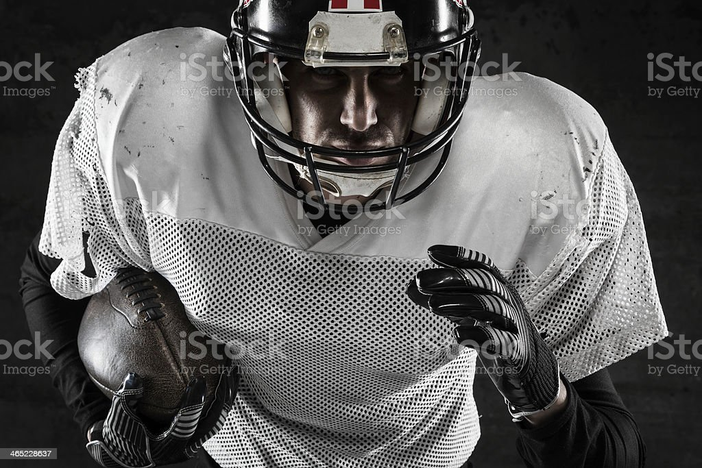 Portrait of american football player holding a ball and running stock photo