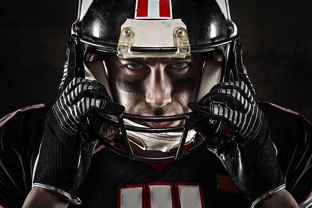 Portrait of American football player in jersey and helmet Portrait of american football player looking at camera with intense gaze safety american football player stock pictures, royalty-free photos & images
