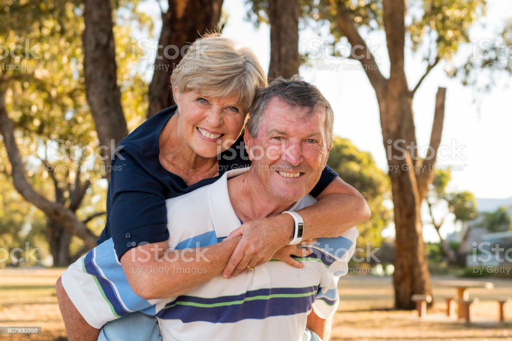 Portrait de la belle américaine senior et heureux couple mature autour de 70 ans montrant l'amour et l'affection souriant ensemble dans le parc ayant un romantique marche mari porter femme sur son dos photo libre de droits