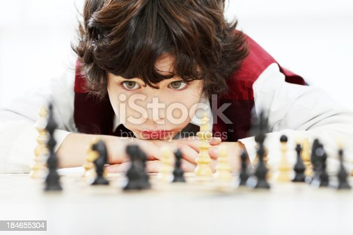 Portrait of an 8 year old boy thinking and playing chess game.