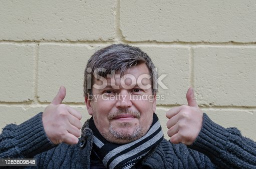 Portrait of an adult man gesticulating with two hands against light wall. Middle-aged man holds his thumbs up. Body language.