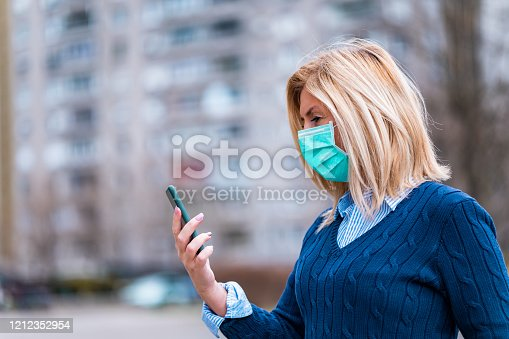 Portrait of an adult caucasian woman wearing a protective face mask and using a mobile phone outdoors.