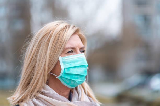 Porträt einer erwachsenen Frau, die eine schützende Gesichtsmaske im Freien trägt – Foto