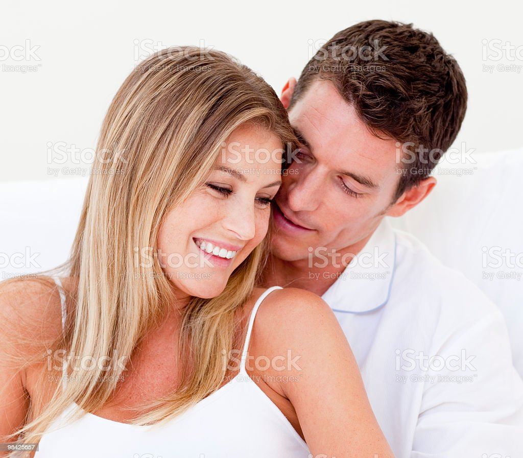 Portrait of an affectionate couple sitting on bed royalty-free stock photo