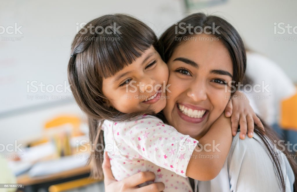 Portrait of an affectionate girl hugging her teacher at school stock photo