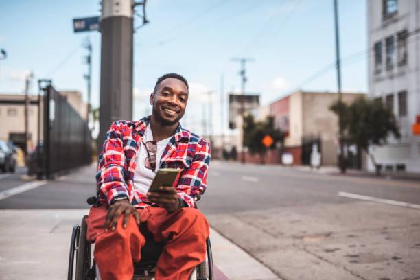 Porträt eines afroamerikanischen Behinderten im Rollstuhl mit Smartphone im Freien – Foto