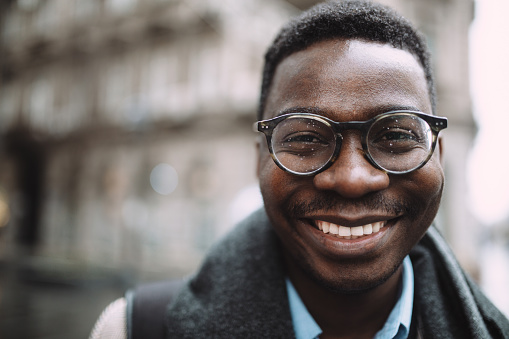 Portrait of a happy young African American man, standing in the rain and smiling