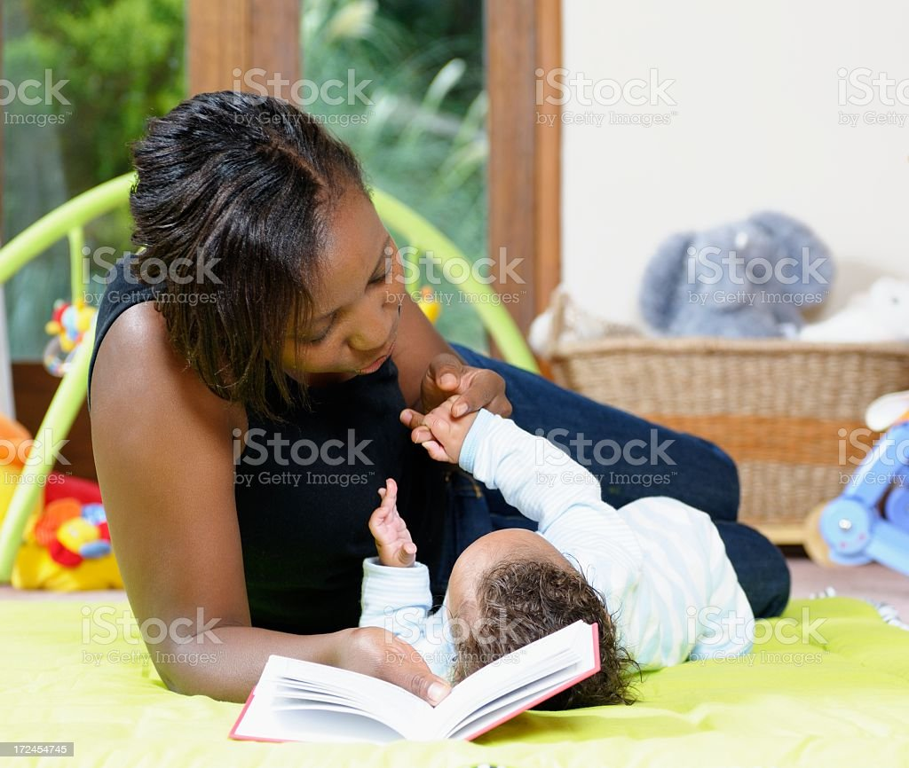 Portrait Of An African American Woman Enjoying Storytime With Baby royalty-free stock photo