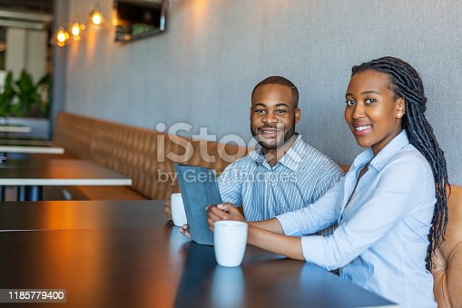 624700110istockphoto Portrait of an African Businessman and Businesswoman Having a Casual Meeting 1185779400
