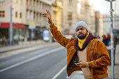 istock Portrait of an African Man Who is Standing in the City Street and Trying to Catch a Ride. 1319585168