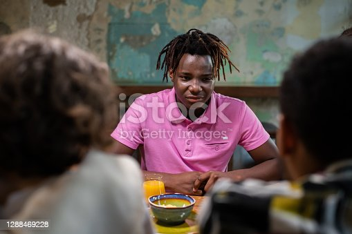 A portrait of an african-american boy talking to his friends in a cafe.