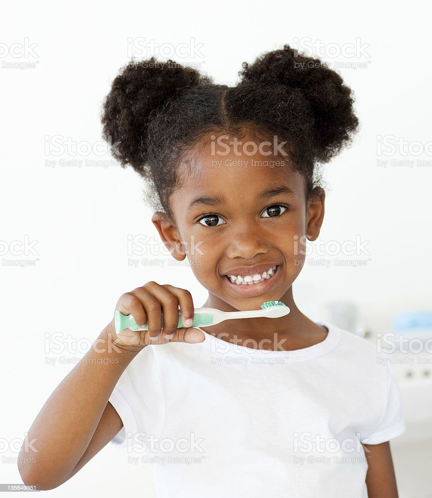 Portrait of an Afro-american girl brushing her teeth stock photo
