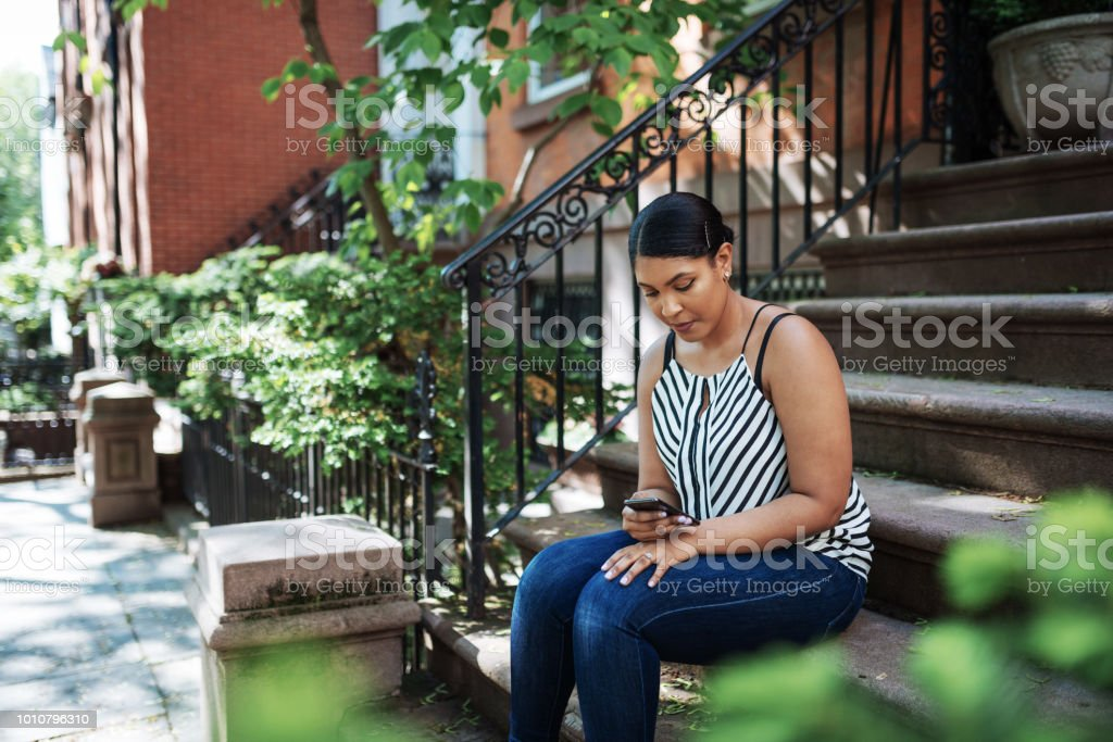 Portrait of obese Afro-Caribbean woman with smart phone outdoors stock photo