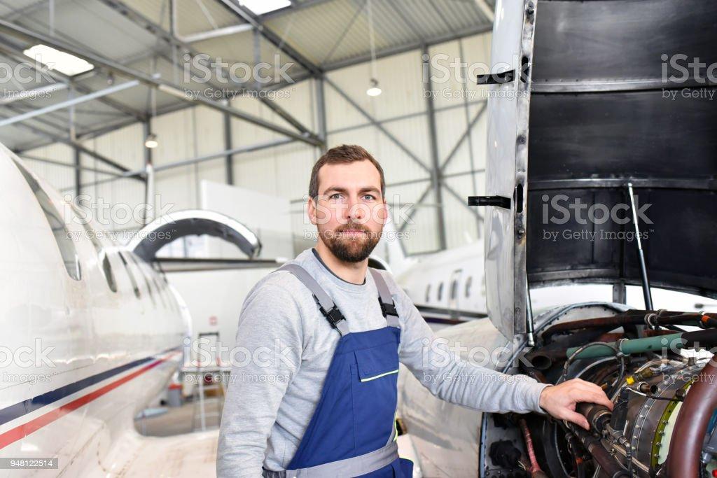 Porträt von Flugzeugmechaniker in einem Hangar mit Jets am Flughafen - Check-das Flugzeug für Sicherheit und technische Funktion - Lizenzfrei Anpassen Stock-Foto