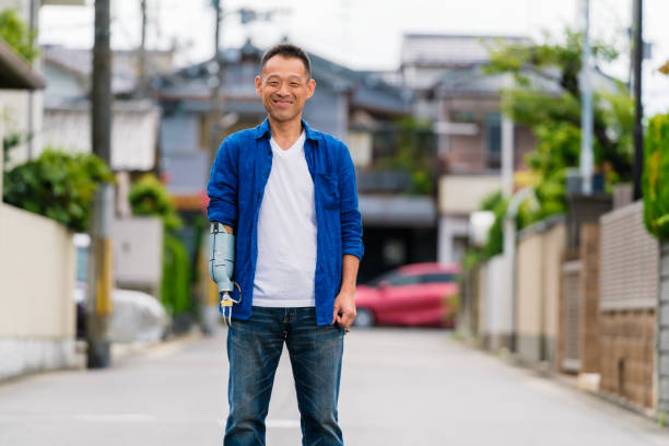 Portrait of an amputee mid adult man stood outdoors Portrait of an amputee mid adult man stood outdoors. Osaka, Japan. September 2017 prosthetic hand stock pictures, royalty-free photos & images