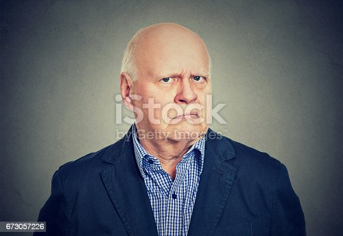 istock Portrait of an angry, grumpy senior business man, isolated on gray background 673057226