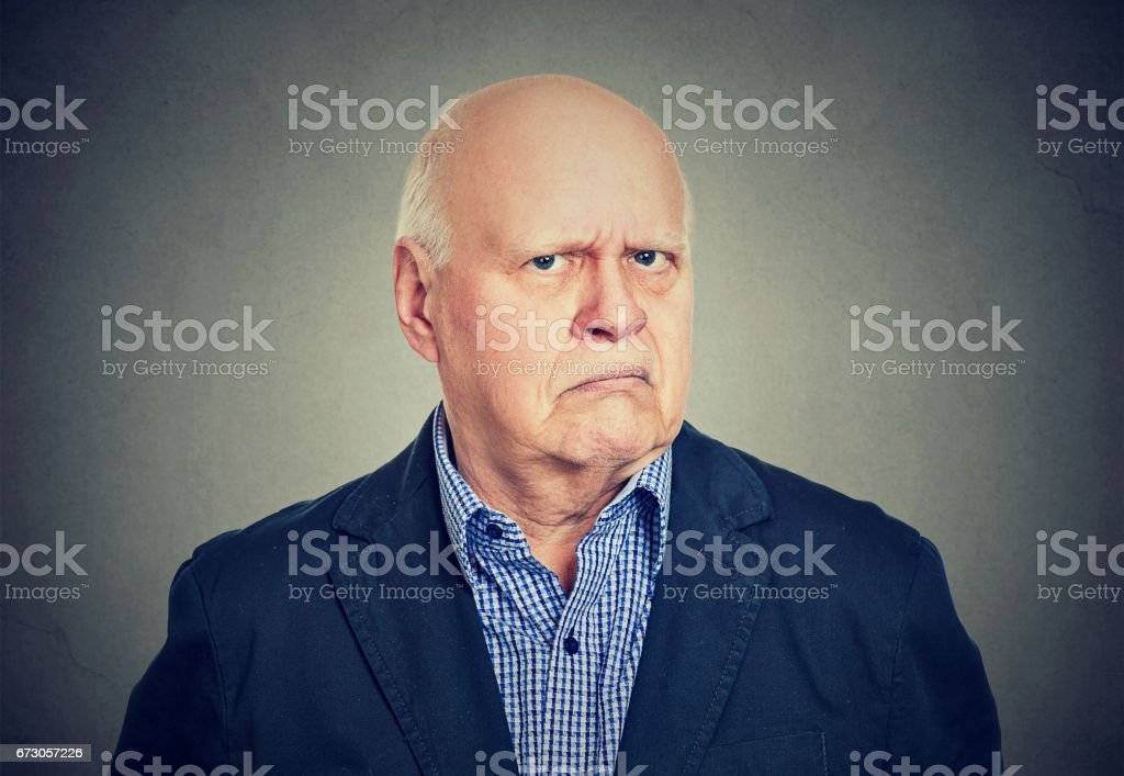 Portrait of an angry, grumpy senior business man, isolated on gray background stock photo