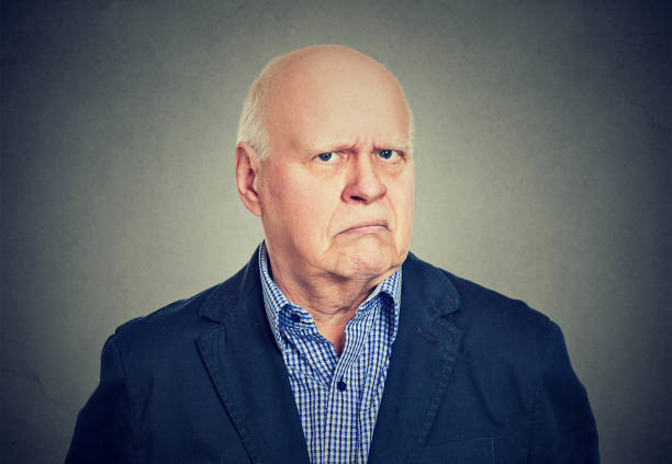 portrait of an angry, grumpy senior business man, isolated on gray background - frowning stock photos and pictures